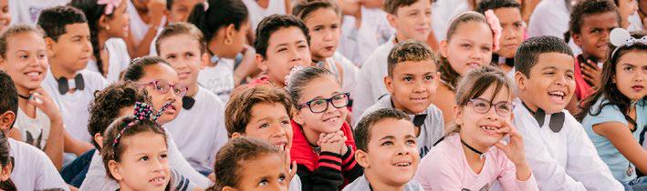 Foto de crianças sorridentes entre 6 e 8 anos atentas a apresentação do Concerto Didático Brasil de Tuhu.
